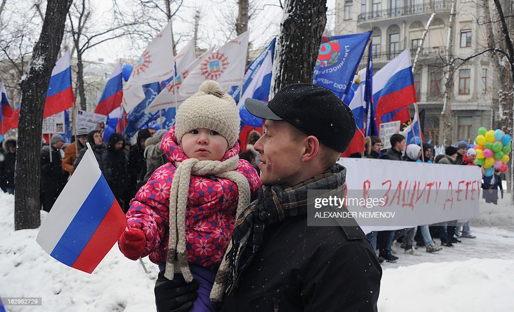 A man walks with his child, as activists from pro-Kremlin children's advocacy groups march through Moscow on March 2, 2013 to call on authorities to ban all foreign adoptions and demand the return of an adopted boy whose brother died in Texas. The banner reads 'The March for Protection of the Children'.