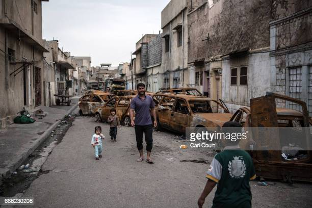 A man walks with his children past burnt out cars in a street in west Mosul on April 13 2017 in Mosul Iraq As the Mosul offensive enters its sixth...