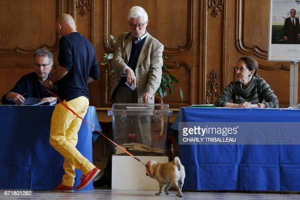 A man walks with his dog as he prepares to cast his ballot at a polling station in Caen northwestern France on April 23 2017 during the first round...
