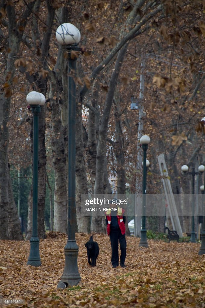 A man walks with his dog during a cold fall morning in Santiago, Chile, on June 16, 2009