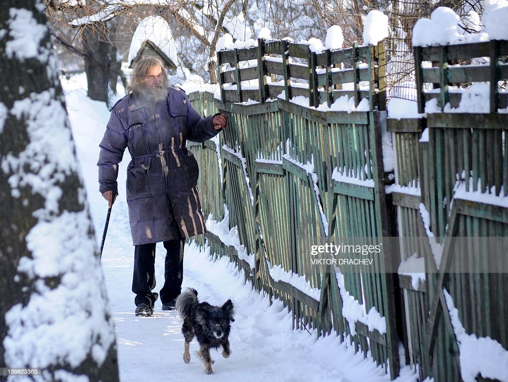 A man walks with his dog in the Belarus capital Minsk, on January 21, 2013. Snow fell today across Minsk as the temperatures dropped to -12 C (10 F). AFP PHOTO / VIKTOR DRACHEV