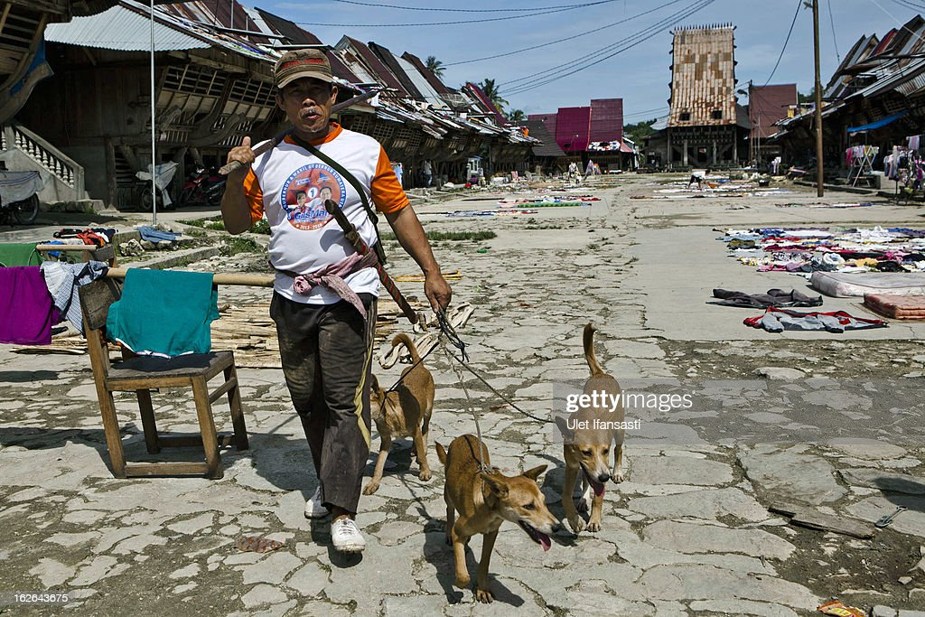A man walks with his dogs as going to hunt in Bawomataluwo village on February 22, 2013 in Nias Island, Indonesia. Some of historians and archaeologists estimated this is one of remaining Megalithic cultures in existence today. Stone Jumping is a traditional ritual, with locals leaping over large stone towers, which in the past resulted in serious injury and death. Stone jumping in Nias Island was originally a tradition born of the habit of inter tribal fighting on the island of Nias.