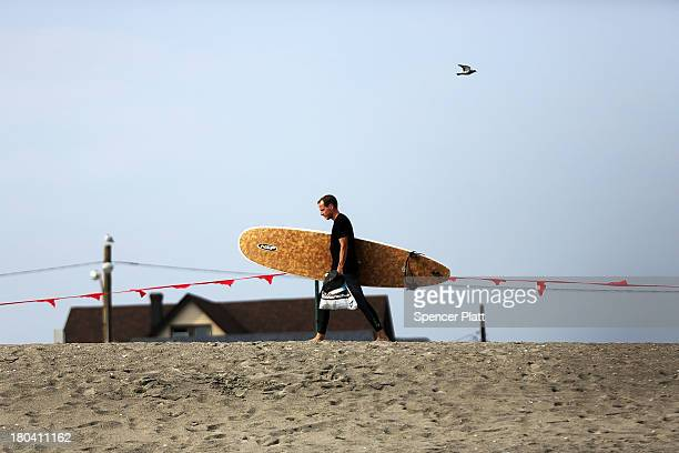 A man walks with his surfboard in the late afternoon at Rockaway Beach on September 12 2013 in the Queens borough of New York City Despite the...