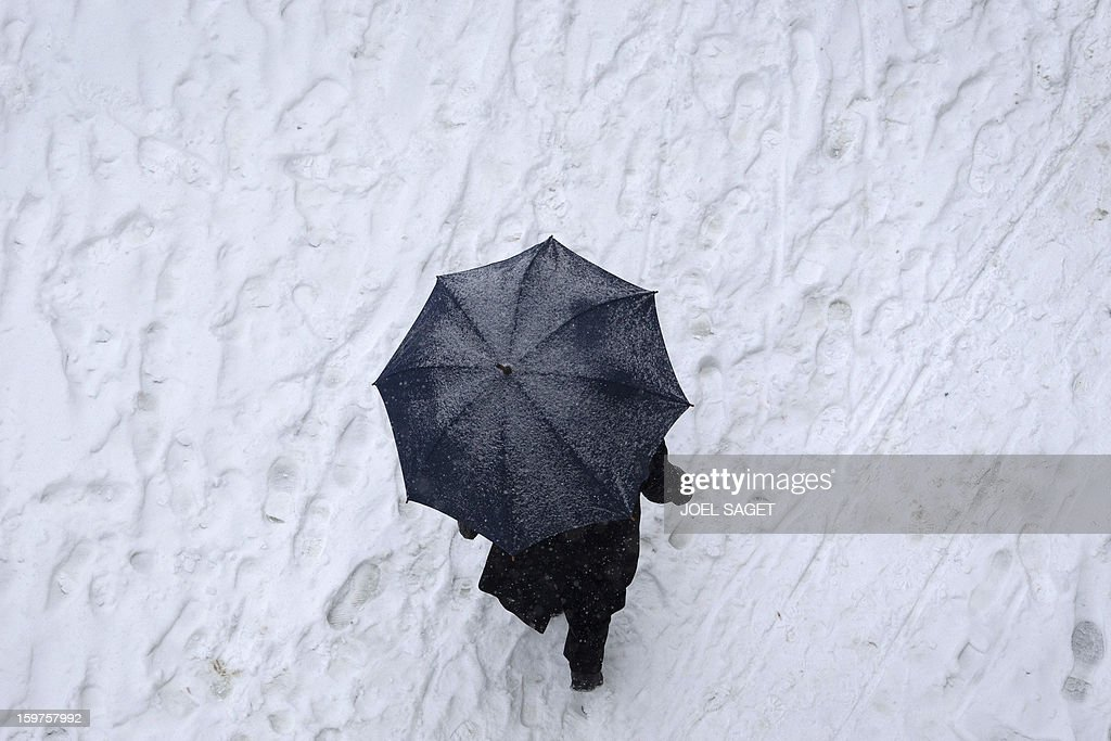 A man walks with his umbrella on a snow covered street, on January 20, 2013 in Paris, as snow falls over the French capital.
