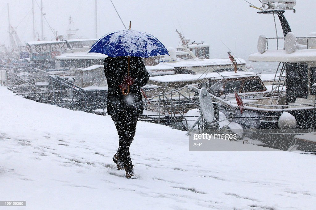 A man walks with his umbrella on the Anatolian side of Istanbul on January 9, 2013. Heavy snowfall blanketed Turkey's commercial hub Istanbul, a city of 15 million, paralysing daily life, disrupting air traffic and land transport. AFP PHOTO/MIRA
