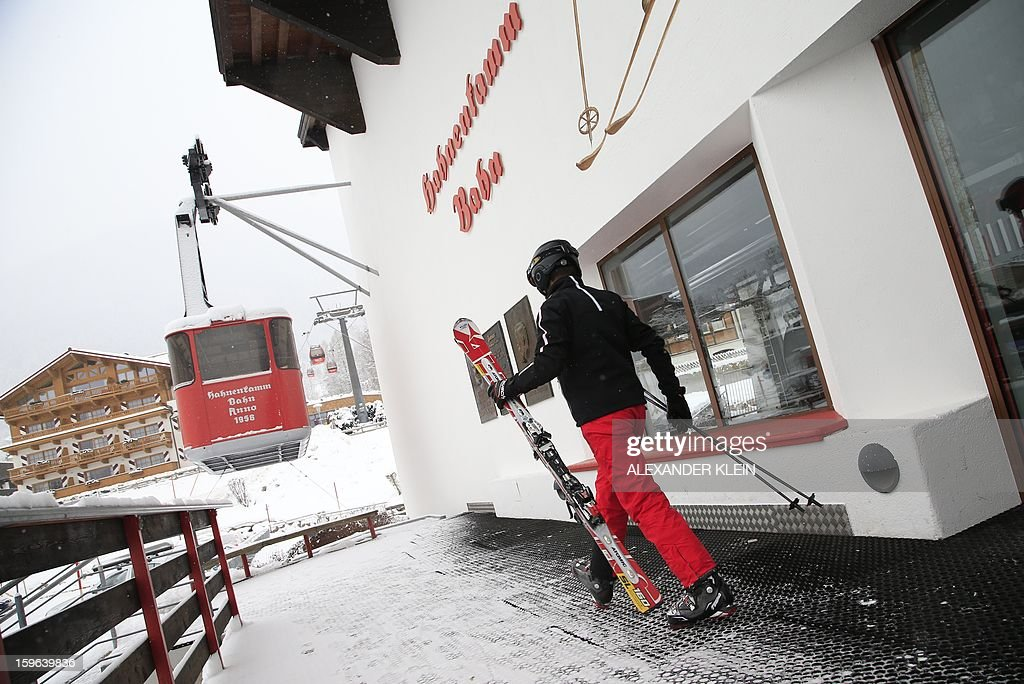 A man walks with skis after exhiting the Hahnenkamm cable car during a snowy day in Kitzbuhel January 17, 2013. Kitzbuhel will host the 73rd edition of the Kitzbuhel Hahnenkamm ski race from January 22, to January 27, 2013, as part of the 2013 FIS Ski World Cup.