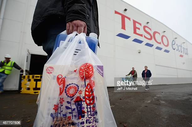 A man walks with Tesco supermarket bags on October 23 2014 in Glasgow ScotlandTesco one of Britains biggest supermarkets has announced a 919% plunge...