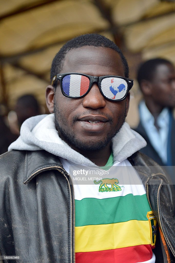 A man wares glasses with painted French flag and French rooster symbol during a demonstration, organized by Malian associations, in support of the liberation forces of Mali on January 26, 2013 in Montreuil, near Paris. Placard reads 'For a united Mali, against terrorism'.