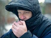 Man wearing hood warming his hands, outdoor horizontal shot
