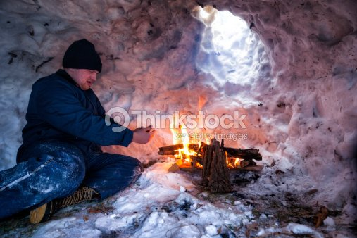 man warms hands near fire inside igloo stock photo. Black Bedroom Furniture Sets. Home Design Ideas