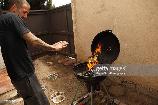 Man warms hands over BBQ