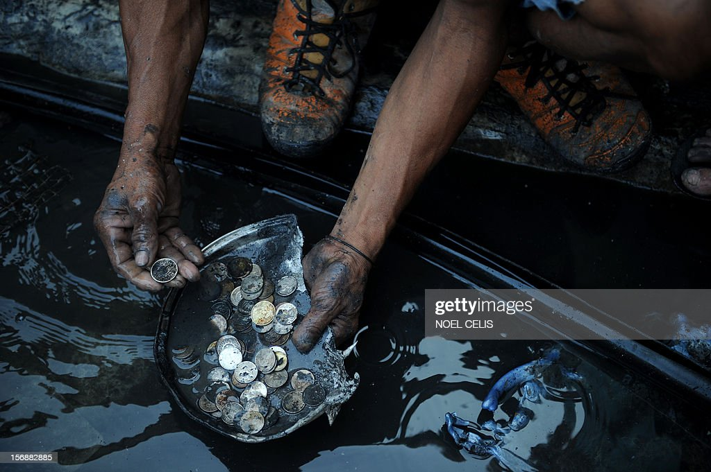 A man washes and displays coins that he recovered among the burnt debris of destroyed houses in Manila on November 24, 2012 after an overnight fire razed a slum area. Three children died during the fire and almost 150 people were affected according to local media report.