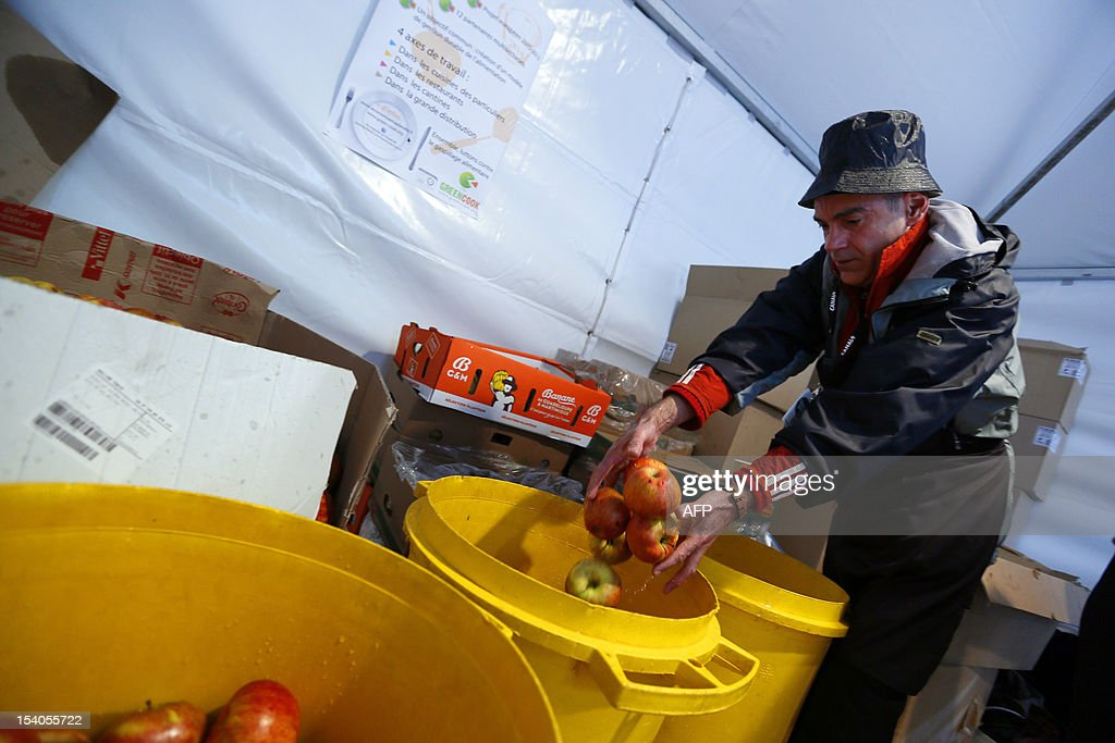A man washes apples during an event to raise awareness of the food waste on October 13, 2012 at the Place de l'Hotel de Ville in Paris. Five thousand people were invited to enjoy a giant curry prepared using 800 kg of twisted carrots and uncalibrated vegetables that supermarkets refuse to buy from producers and which usually end in disposal. 'While one billion people suffer from malnutrition in the world, a third of the food produced ends up in the trash! I am green since I was 4 years' said Tristram Stuart, British author and activist.