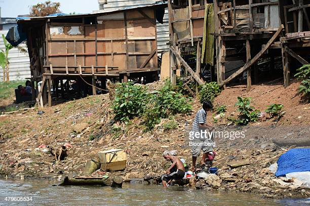 A man washes dishes in a river in front of shanty houses standing perched on stilts in Jakarta Indonesia on Tuesday June 23 2015 Having watched his...