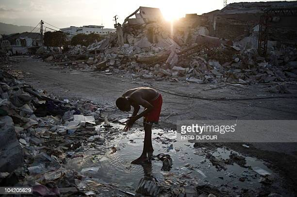 A man washes on the street in PortauPrince on January 31 2010 Quakehit Haiti will need at least a decade of painstaking reconstruction aid chiefs and...