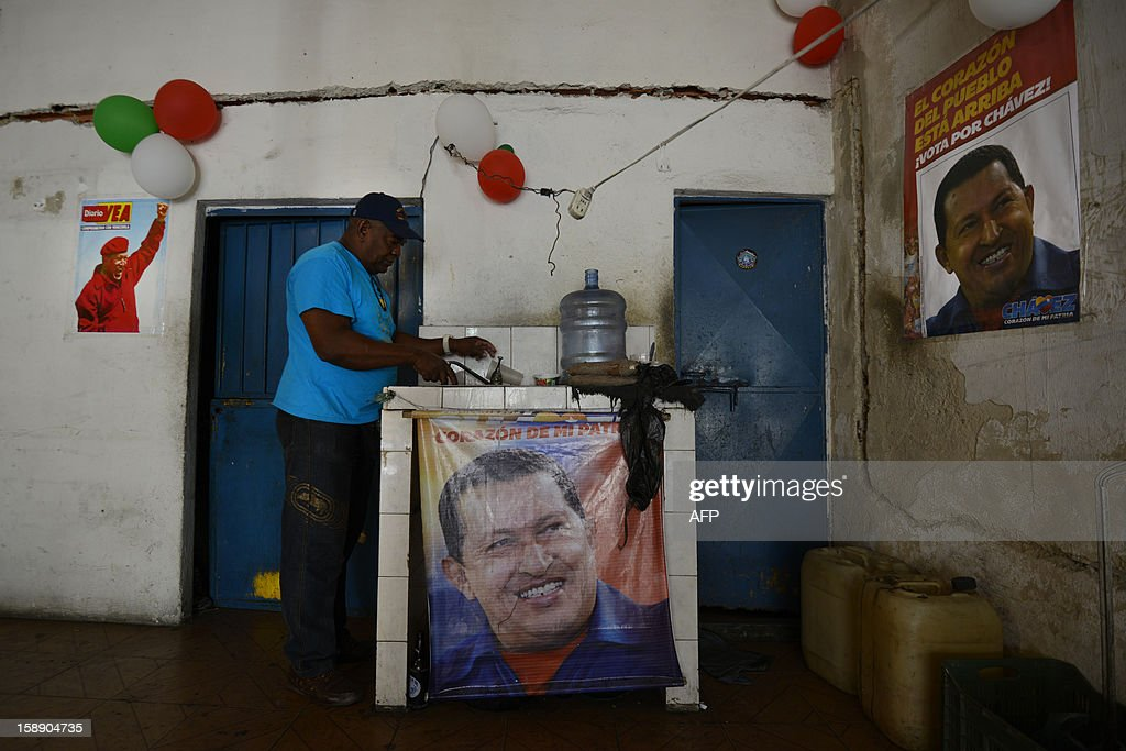 A man washes the dishes surrounded by posters of Venezuelan President Hugo Chavez at his home in Caracas, on January 3, 2013. Top Venezuelan officials gathered in Cuba on Thursday amid growing demands for news about cancer-stricken President Hugo Chavez' condition, days before he is to be sworn in for another term. The Venezuelan president has not been seen since he underwent a long and complicated surgery for a recurrence of cancer 23 days ago, and officials have acknowledged that his recovery has been difficult.