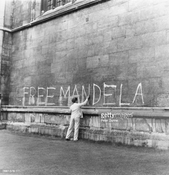 A man washing a 'Free Mandela' slogan off the side of King's College Chapel Cambridge