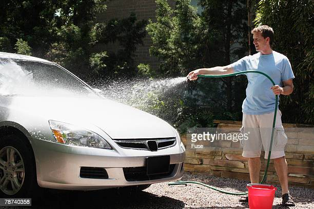 Man Washing Car in Driveway