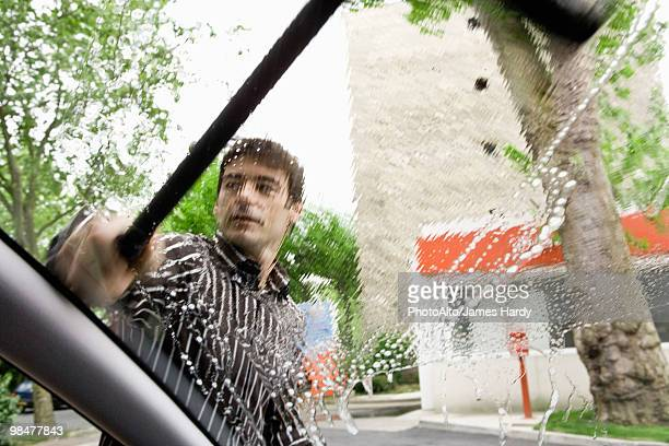 Man washing car windshield with squeegee