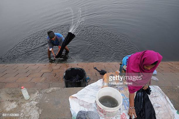 A man washing clothes on the banks of river Yamuna during a cold weather as there is sudden drop in the weather due to rain on January 7 2017 in...