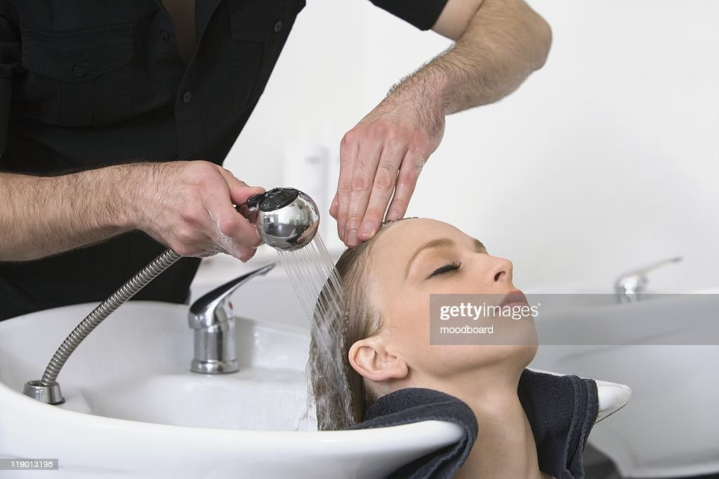 Man washing customers hair in the hairdressers