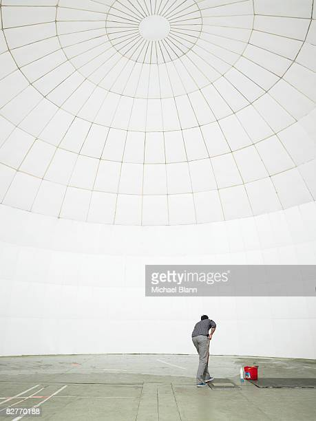 man washing floor with bucket and mop