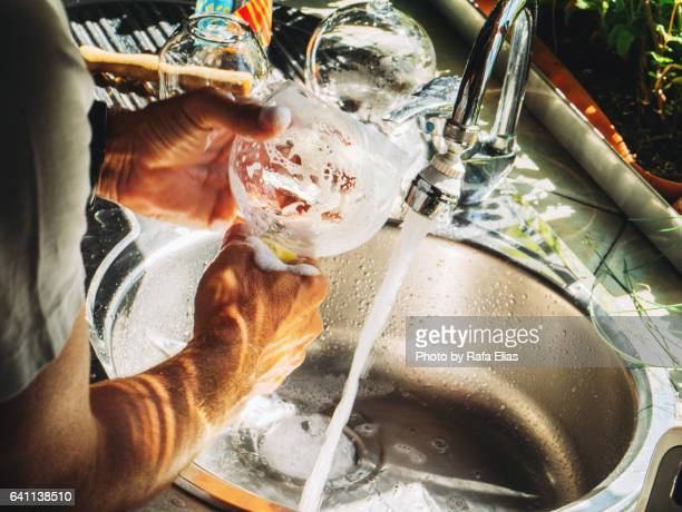 Man washing glass in the kitchen