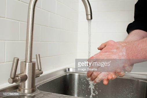 Man washing hands in kitchen sink : Stock Photo