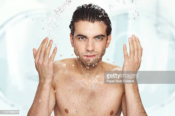 Man washing his face with water in the bathroom