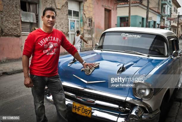 Man washing his vintage car in the street