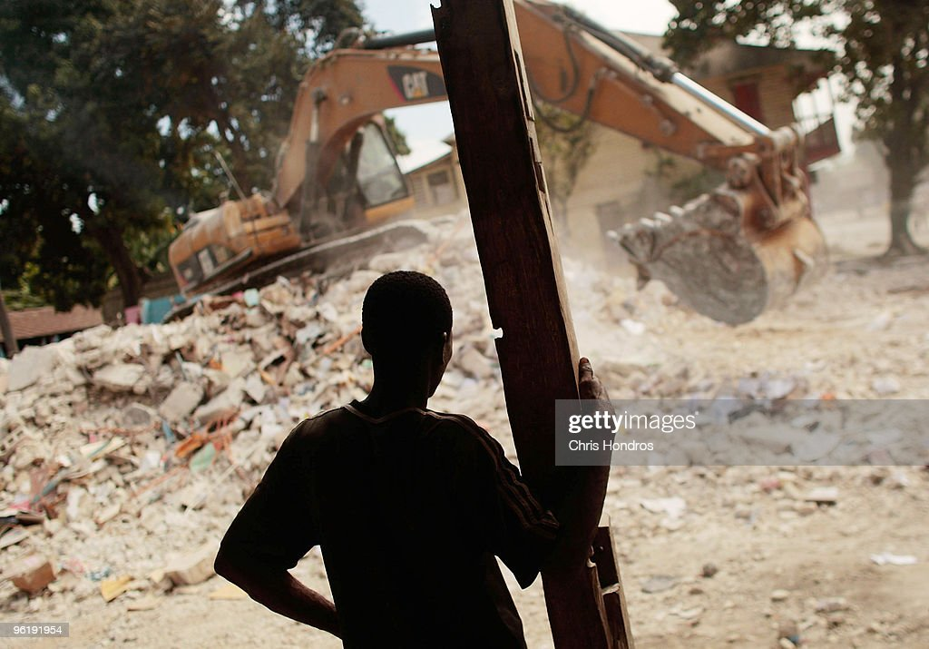 A man watches a backhoe sift through the rubble of a primary school January 26, 2010 in Legoane, Haiti. The historic town of Legoane was near the epicenter of the 7.0 earthquake, that displaced millions and killed an estimated at 150 thousand.