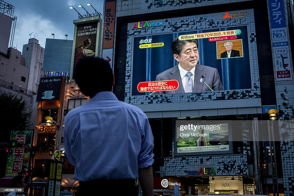 A man watches a big screen showing a live broadcast of Japanese Prime Minister, <a gi-track='captionPersonalityLinkClicked' href=/galleries/search?phrase=Shinzo+Abe&family=editorial&specificpeople=559017 ng-click='$event.stopPropagation()'>Shinzo Abe</a> as he delivers his WWII Anniversary Statement on August 14, 2015 in Tokyo, Japan. Japanese Prime Minister Abe delivered a war anniversary statement ahead of the anniversary of Japan's defeat in the second world war. The statement included such keywords as 'apology from the heart,' 'colonial rule,' and 'aggression.'