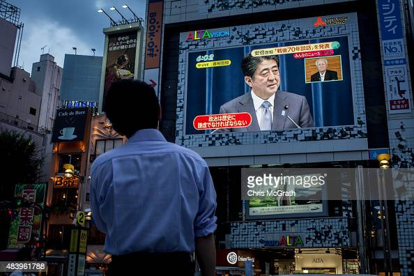 A man watches a big screen showing a live broadcast of Japanese Prime Minister Shinzo Abe as he delivers his WWII Anniversary Statement on August 14...