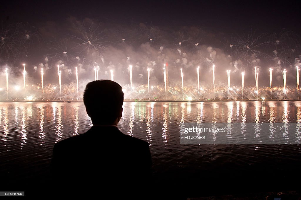 A man watches a fireworks display to mark 100 years since the birth of North Korea's founder Kim Il-Sung in Pyongyang on April 15, 2012. North Korea's new leader Kim Jong-Un delivered his first public speech and vowed to push for 'final victory' for his impoverished state despite a failed rocket launch two days ago, as the country celebrated the 100th anniversary of former leader Kim Il-Sung. AFP PHOTO / Ed Jones