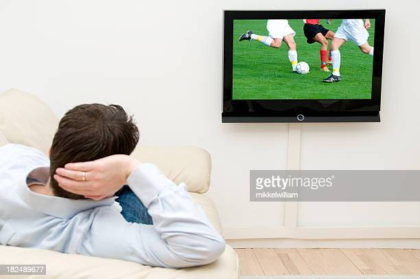 Uomo esegue una partita di calcio per la tv a casa