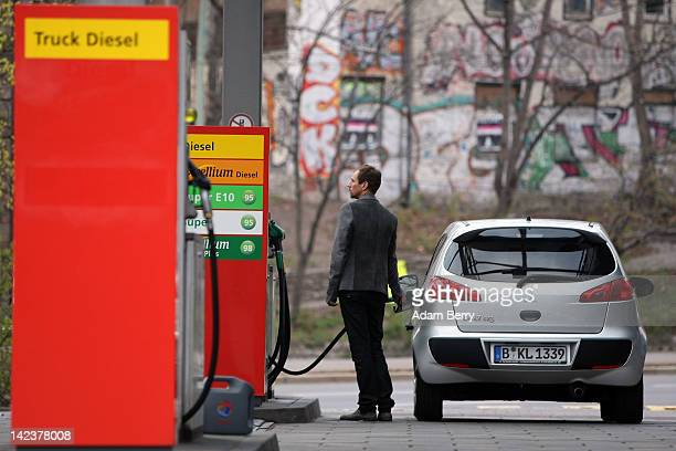 A man watches a fuel pump as he fills his car at a gas pump at a Total gas station on April 3 2012 in Berlin Germany The Bundesrat one of the five...