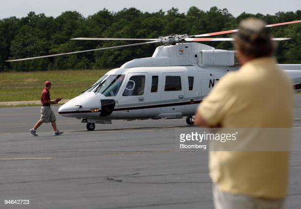 A man watches a helicopter on the tarmac of the East Hampton Airport in East Hampton New York on Aug 19 2007 Even with turbulent financial markets...