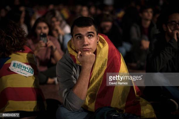 A man watches a large screen showing the speech of the Spain's Prime Minister Mariano Rajoy at Plaza Catalunya on October 1 2017 in Barcelona Spain...