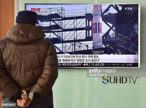 A man watches a news report on North Korea's planned rocket launch as the television screen shows file footage of North Korea's Unha3 rocket which...