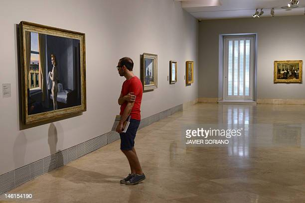 A man watches a painting by US artist Edward Hopper entitled 'Morning in a City' at the ThyssenBornemisza Museum in Madrid on June 11 2012 AFP PHOTO/...