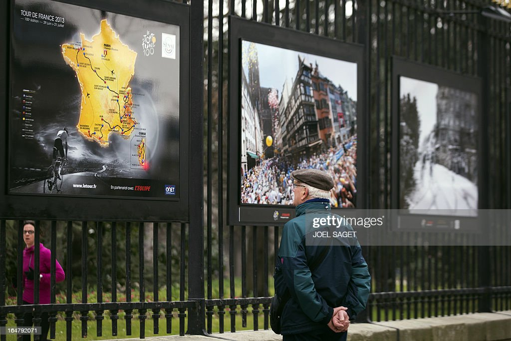 A man watches a photo exhibition dedicated to the 100th anniversary of the Tour de France cycling race on the fences of the Luxembourg garden on March 28, 2013 in Paris.