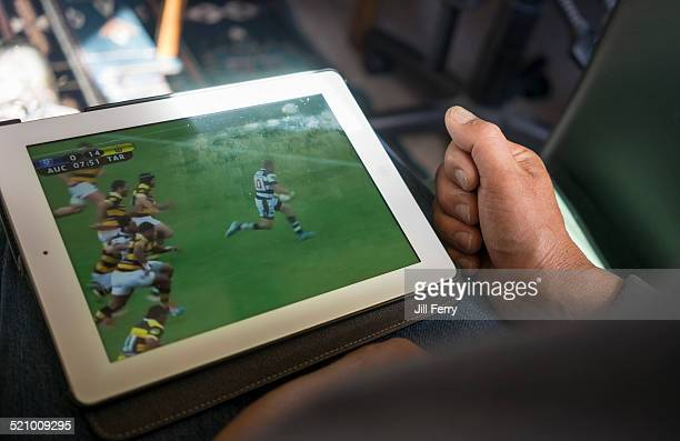 A man watches a rugby match on his tablet