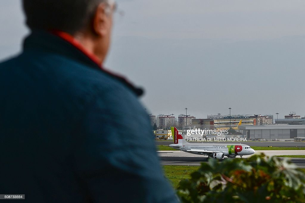 A man watches a TAP airline plane as it taxis at Lisbon's Airport on February 6, 2016. Portugal's new Socialist government said Saturday it had lifted its stake in TAP to 50 percent from 39 percent in line with a manifesto pledge targeting re-nationalisation. AFP PHOTO / PATRICIA DE MELO MOREIRA / AFP / PATRICIA DE MELO MOREIRA