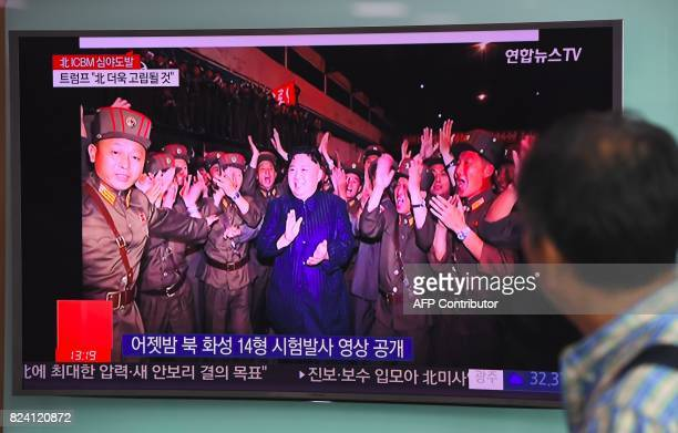 TOPSHOT A man watches a television screen showing a video footage of North Korean leader Kim JongUn during the North's latest test launch of an...