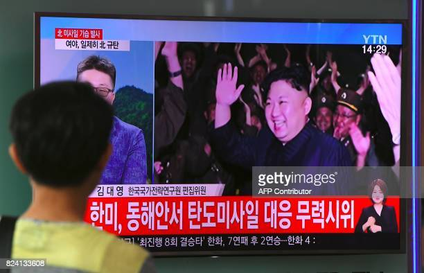 A man watches a television screen showing a video footage of North Korean leader Kim JongUn celebrating his country's latest test launch of an...