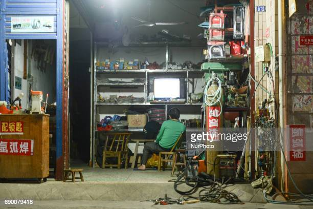 A man watches a TV inside a small family business in Liling On Thursday September 22 2016 in Liling Zhuzhou Hunan Province China
