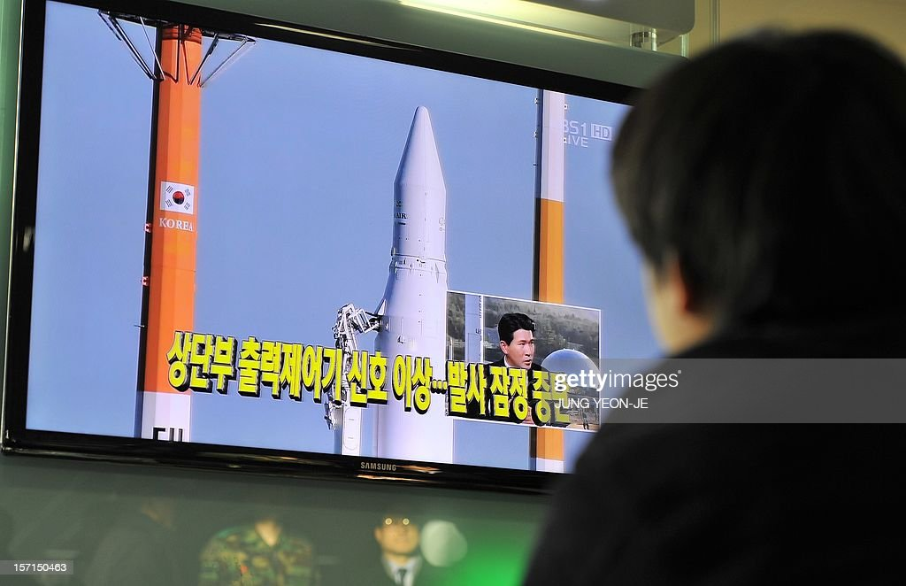 A man watches a TV screen broadcasting live footage on South Korea's third attempt of a rocket launch, at a railway station in Seoul on November 29, 2012. South Korean space officials halted the countdown on a crucial rocket launch, aimed at placing a satellite in orbit and announcing the country's entry into an elite global space club.