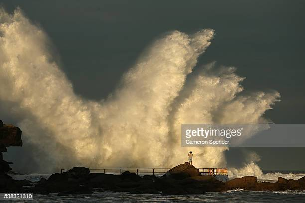 A man watches a wave hit a rock pool at Curl Curl beach as large swell hits the East Coast of Australia on June 6 2016 in Sydney Australia Torrential...