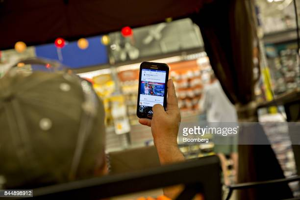 A man watches a weather report on his mobile phone while waiting inside a Lowe's Cos store ahead of Hurricane Irma in Tampa Florida US on Saturday...