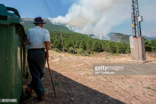 A man watches a wildfire burn near Yeste in south eastern Spain on July 27 2017 Fires ravaged bone dry pine forests and is still not under control...